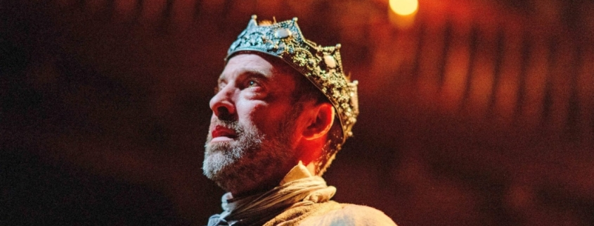 king macbeth stands under candles