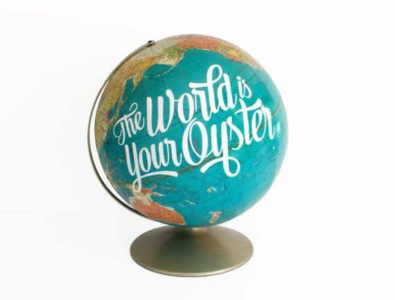 The world's your oyster quote on a globe, with white background