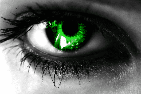 a green eye on black and white close up of an eye, representing the green-eyed monster